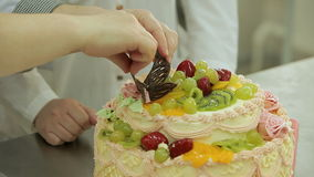Las figuras hechas en casa del chocolate son puestas en una torta de la crema de los arty por un maestro cocinero almacen de metraje de vídeo