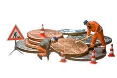 Las figuras miniatura que trabajan en un montón del dólar acuñan Imagen de archivo libre de regalías