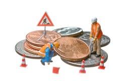 Las figuras miniatura que trabajan en un montón del dólar acuñan Imagen de archivo