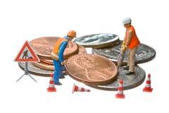Las figuras miniatura que trabajan en un montón del dólar acuñan fotografía de archivo