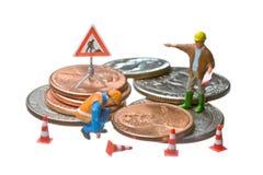 Las figuras miniatura que trabajan en un montón del dólar acuñan Fotos de archivo libres de regalías