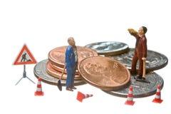 Las figuras miniatura que trabajan en un montón del dólar acuñan Foto de archivo