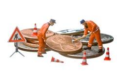 Las figuras miniatura que trabajan en un montón del dólar acuñan Imágenes de archivo libres de regalías