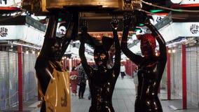 Las figuras vestidas en trajes del látex presentan delante de la cámara como espectadores pasan cerca para observarlos Los caract metrajes