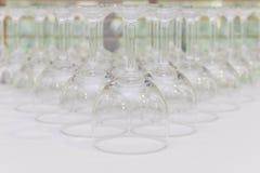 las filas de la copa de vino vacía basan en la tabla blanca Foto de archivo