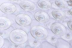 las filas de la copa de vino vacía basan en la tabla blanca Imagenes de archivo