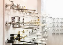 Las filas de los nuevos grifos para el cuarto de baño en la fontanería hacen compras imagen de archivo libre de regalías