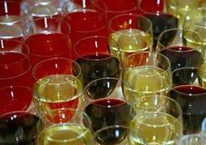 las filas simétricas de los vidrios de cóctel llenaron de diversas bebidas coloreadas en la barra Foto de archivo libre de regalías
