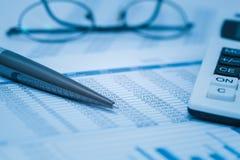 Las finanzas, análisis financiero, considerando consideran hoja de cálculo con los vidrios y la calculadora de la pluma en azul C Fotografía de archivo