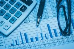 Las finanzas, análisis financiero, considerando consideran hoja de cálculo con los vidrios y la calculadora de la pluma en azul C Foto de archivo