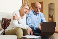 Las finanzas de la lectura de la familia documentan juntas y con el ordenador portátil Fotografía de archivo
