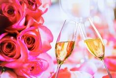 Las flautas de champán con las burbujas de oro en rosas de la boda florecen el fondo Imagen de archivo