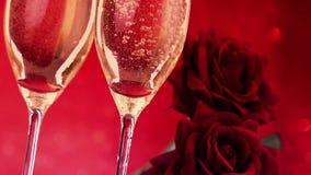 Las flautas de champán de colada con las burbujas acercan a rosas rojas en fondo, amor y día de San Valentín rojos del bokeh almacen de metraje de vídeo