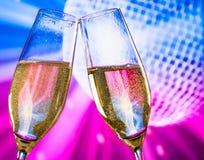 Las flautas de champán con las burbujas de oro hacen alegrías en chispear fondo azul y violeta de la bola de discoteca Imagen de archivo libre de regalías
