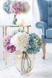 Las flores acercan al sofá azul Imagen de archivo