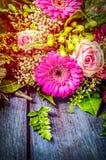 Las flores agrupan con el gerbera y las rosas en fondo de madera azul Foto de archivo libre de regalías