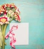 Las flores agrupan con la tarjeta de felicitación blanca en blanco y la cinta rosada en fondo azul elegante lamentable de la turq Foto de archivo libre de regalías