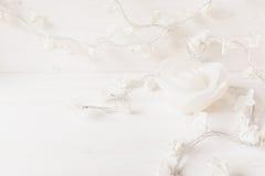 Las flores blancas y la vela de papel subieron en el fondo de madera blanco Imagen de archivo libre de regalías