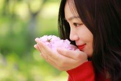 Las flores causual descuidadas libres del olor de la muchacha de la belleza en parque de la primavera disfrutan de tiempo libre Imágenes de archivo libres de regalías