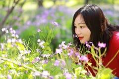 Las flores causual descuidadas libres del olor de la muchacha de la belleza en parque de la primavera disfrutan de tiempo libre Foto de archivo libre de regalías
