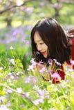 Las flores causual descuidadas libres del olor de la muchacha de la belleza en parque de la primavera disfrutan de tiempo libre Imagenes de archivo