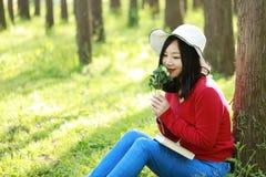 Las flores chinas asiáticas felices del olor de la sonrisa de la muchacha de la belleza de la mujer y leído un libro en magro del Imagen de archivo libre de regalías