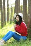 Las flores chinas asiáticas felices del olor de la sonrisa de la muchacha de la belleza de la mujer y leído un libro en magro del Imágenes de archivo libres de regalías