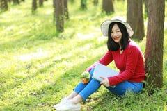 Las flores chinas asiáticas felices del olor de la sonrisa de la muchacha de la belleza de la mujer y leído un libro en magro del Fotografía de archivo libre de regalías