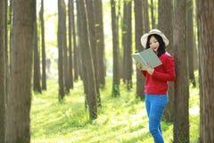 Las flores chinas asiáticas felices del olor de la sonrisa de la muchacha de la belleza de la mujer y leído un libro en magro del Foto de archivo libre de regalías