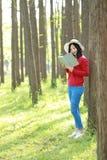 Las flores chinas asiáticas felices del olor de la sonrisa de la muchacha de la belleza de la mujer y leído un libro en magro del Foto de archivo