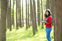 Las flores chinas asiáticas felices del olor de la sonrisa de la muchacha de la belleza de la mujer y leído un libro en magro del Imagen de archivo