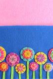 Las flores coloridas del fieltro fijaron en un fondo azul y rosado con el espacio de la copia para el texto La mano hace las flor Fotografía de archivo