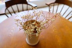 Las flores de la decoración se colorean maravillosamente en la tabla en una cafetería imagenes de archivo