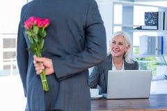 Las flores de ocultación del hombre de negocios detrás apoyan para el colega Fotos de archivo libres de regalías
