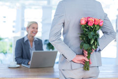 Las flores de ocultación del hombre de negocios detrás apoyan para el colega Fotografía de archivo libre de regalías