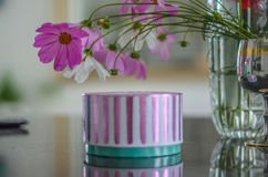 Las flores del florero se inclinaron sobre la caja con un regalo Imagen de archivo