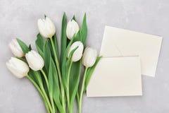 Las flores del tulipán de la primavera y la tarjeta de papel en la opinión de sobremesa de piedra gris en plano ponen estilo Salu Imagenes de archivo