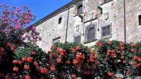 Las flores entregan una casa medieval Imagenes de archivo