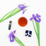 Las flores, los accesorios del ` s de las mujeres y el té azules asaltan en el fondo blanco Endecha plana, visión superior Imagen de archivo libre de regalías