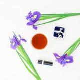 Las flores, los accesorios del ` s de las mujeres y el té azules asaltan en el fondo blanco Endecha plana, visión superior Fotos de archivo