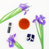 Las flores, los accesorios del ` s de las mujeres y el té azules asaltan en el fondo blanco Endecha plana, visión superior Fotos de archivo libres de regalías