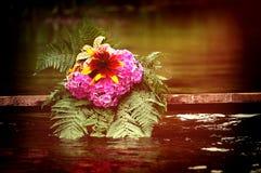 Las flores mienten en el viejo tablero con agua Imagenes de archivo