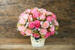 Las flores plásticas con el fondo de madera en vintage representan el estilo, equipo interior del hogar, flores fijadas en fondo  fotos de archivo libres de regalías