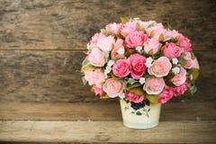 Las flores plásticas con el fondo de madera en vintage representan el estilo, equipo interior del hogar, flores fijadas en fondo  imagen de archivo libre de regalías