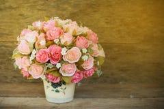 Las flores plásticas con el fondo de madera en vintage representan el estilo, equipo interior del hogar, flores fijadas en fondo  foto de archivo libre de regalías
