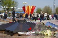Las flores ponen cerca de la llama eterna para el 9 de mayo Imagenes de archivo