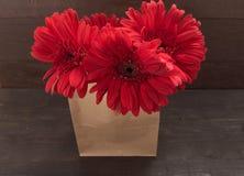 Las flores rojas del gerbera están en el bolso, en el fondo de madera Fotografía de archivo