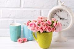 Las flores rosadas de las rosas, el reloj y verde colorido y el azul ahueca agai fotografía de archivo libre de regalías