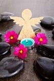 Las flores rosadas del cosmos, la vela azul del tealight y el ángel de la arpillera forman Imagen de archivo libre de regalías