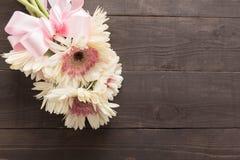 Las flores rosadas y blancas del gerbera con la cinta están en el fondo de madera Foto de archivo